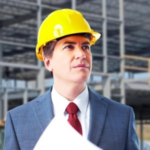 man-in-orange-hard-hat-and-business-suit-with-building-structure-in-the-background